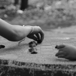 Chess pieces are substituted for small stones because of the school's lack of supplies.