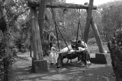 During recess, a group of children gathered around a woven swing.