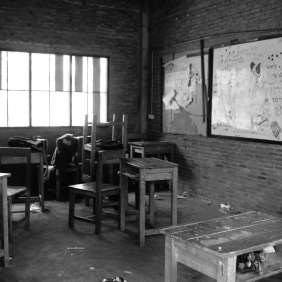 Rusted desks and chairs are scattered across many of the classrooms at the school. During class time, most children choose to sit on the floor.